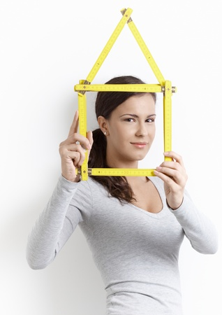 Young female playing with folding rule, forming house, smiling. Stock Photo - 8557457