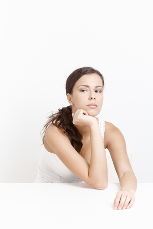Young woman sitting in bad mood over white background. Stock Photo - 8553097