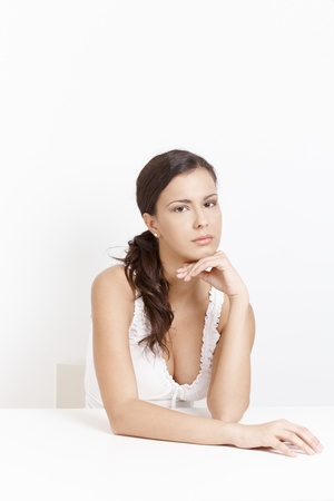 unsmiling: Attractive girl sitting sadly over white background.