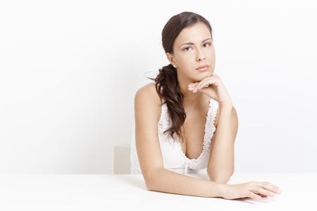 sadly: Travagliata donna seduta, purtroppo, su sfondo bianco.