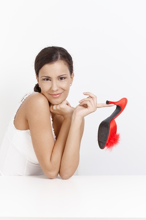 Attractive young girl posing with sexy high heel slippers in hand, smiling. Stock Photo - 8553103