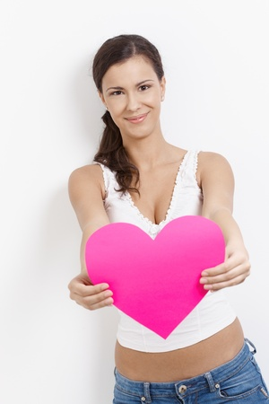 Lovesick young attractive woman smiling happily with pink paper heart in hands. photo
