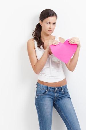 sadly: Lovelorn woman standing sadly with paper heart in hands. Stock Photo