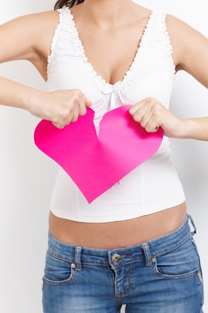 heartbroken: Angry lovelorn young woman tearing pink paper heart apart.