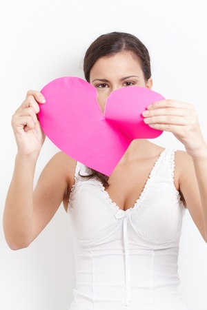 lovelorn: Young lovelorn female tearing paper heart to pieces