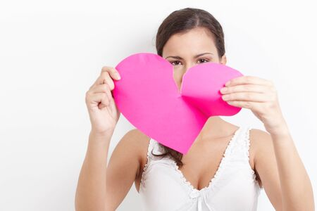 broken relationship: Young woman pulling pink paper heart to pieces. Stock Photo