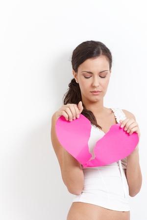 sadly: Cuore spezzato woman holding un cuore di carta nelle mani, guardando tristemente. Archivio Fotografico