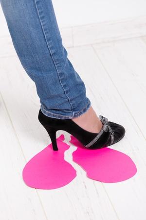 heart break: Female leg wearing jeans and high heel shoes treading on torn paper heart.