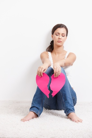 Young lovelorn female sitting on floor with paper heart in hands. photo