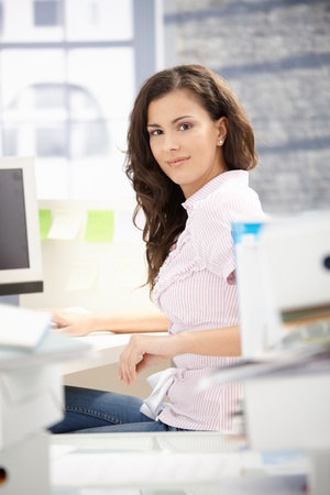 Young secretary working on computer in bright office, smiling.