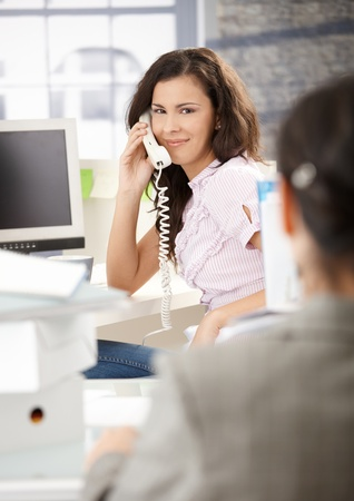 Busy secretary talking on phone in bright office, smiling. photo