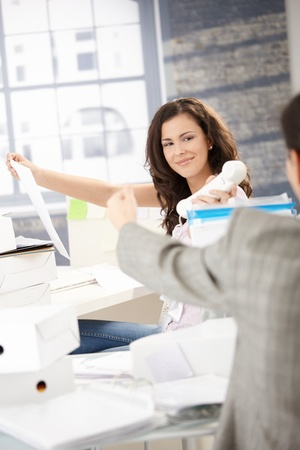 joyous: Joyous female office worker passing phone to colleague in office, smiling.