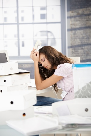 Young girl having headache in office, sitting at desk, holding phone. Stock Photo - 8557565