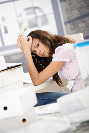 Young secretary having headache in office, sitting at desk desperately. photo
