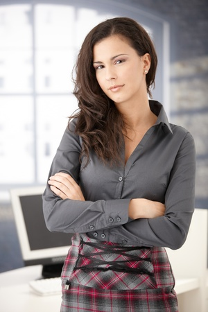 arms crossed: Pretty young casual office worker standing in office arms crossed, smiling.