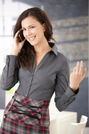 Happy young casual office worker using mobile, smiling in office. Stock Photo - 8558018