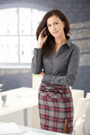 secretary skirt: Attractive young secretary using mobile phone in office.