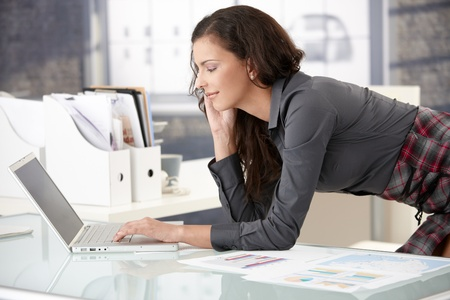 good mood: Attractive young businesswoman browsing internet in office, smiling. Stock Photo