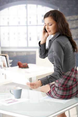 Sexy businesswoman chatting on phone, sitting on desk in office. photo