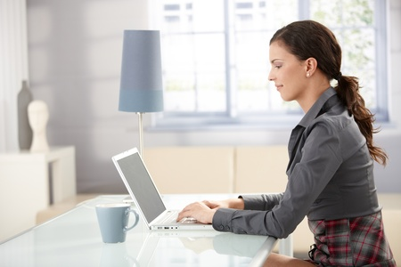 Young female working at home, using laptop, smiling. photo
