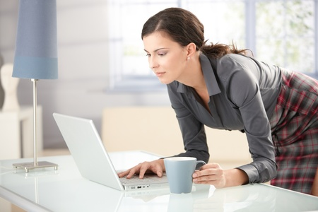 Young female browsing internet at home, drinking tea. Stock Photo - 8553162