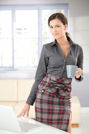 Attractive young woman standing by table, drinking tea, smiling. photo