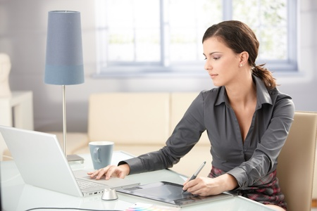Giovane graphic designer lavorano sul portatile utilizzando Tablet PC a casa. Archivio Fotografico
