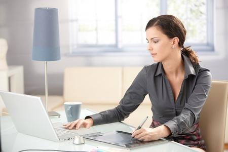 MÅ'ody projektant graficzny pracy na komputerze przenoÅ›nym przy użyciu komputera typu tablet w domu. Zdjęcie Seryjne