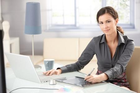 jornada de trabajo: Atractiva joven dise�ador gr�fico utilizando equipos port�tiles y Tablet PC, trabajando en casa, sonriendo.