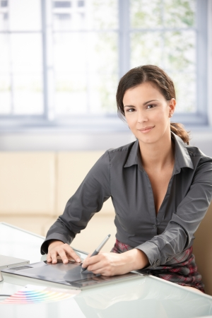Attractive female graphic designer working on tablet, smiling. photo