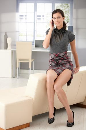 mini skirt: Sexy young woman sitting on sofa, chatting on mobile, wearing mini skirt. Stock Photo