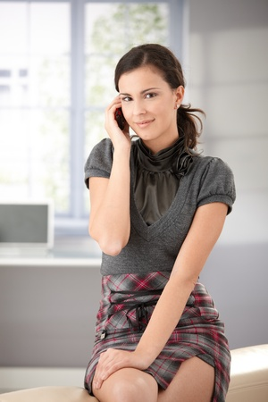 mini skirt: Attractive young girl chatting on mobile phone, smiling.