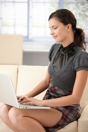 internet profile: Sexy female using laptop at home, browsing internet, smiling.