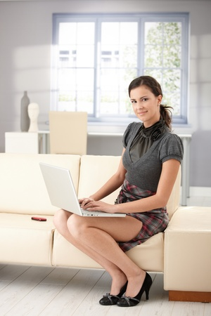 Pretty girl sitting on sofa at home, using laptop, smiling. photo
