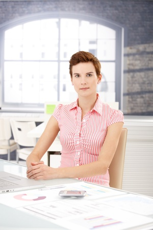 Portrait of young office worker girl sitting at desk, looking at camera. Stock Photo - 8553153