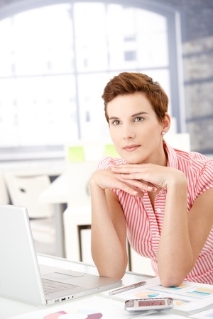Female office worker sitting at desk by laptop computer, thinking. Stock Photo - 8553110
