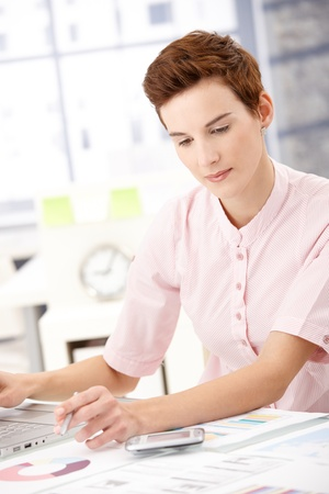 reviewing documents: Young professional woman sitting at desk in office, working with laptop computer, reviewing documents. Stock Photo