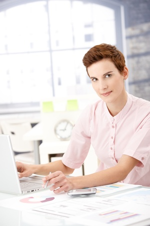 Young businesswoman at work, using laptop computer, holding pen, looking at camera. Stock Photo - 8553105