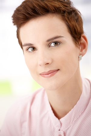 Closeup facial portrait of young woman smiling at camera. photo