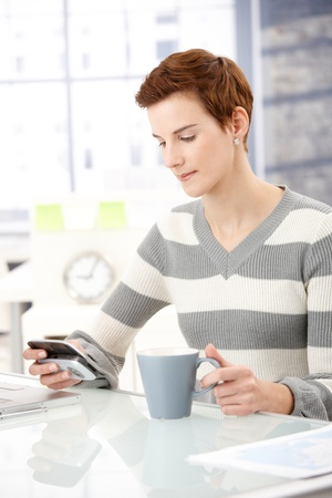 Office worker girl sitting at desk, using smartphone, having coffee. photo