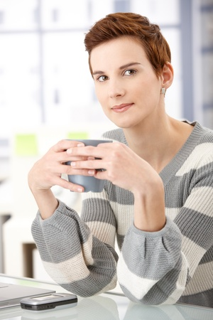 Young woman having coffee break in office by desk, smiling at camera. photo