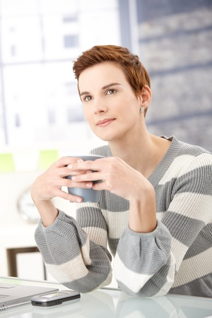 Daydreaming office worker girl sitting at desk with coffee mug handheld. Stock Photo - 8558010