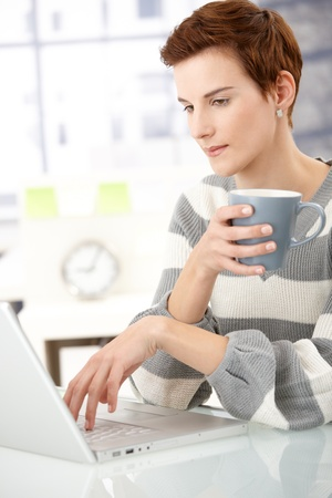 Office girl sitting at desk with mug handheld, working on laptop computer. Stock Photo - 8553249