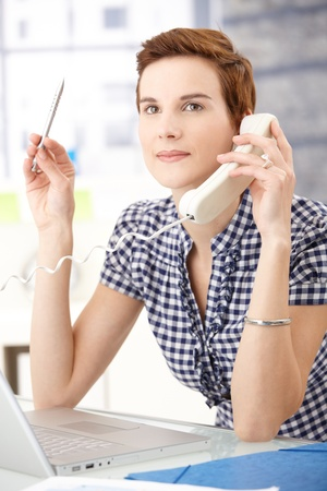 Office worker woman concentrating on landline phone call with pen in hand, looking up smiling. photo