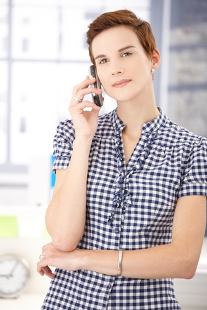 Young woman standing with cellphone, listening to phone call, smiling. Stock Photo - 8553371