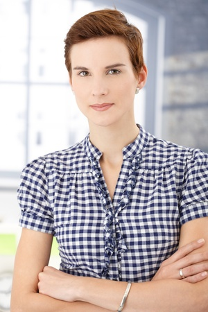 ginger hair: Portrait of short ginger hair woman smiling at camera. with arms folded. Stock Photo