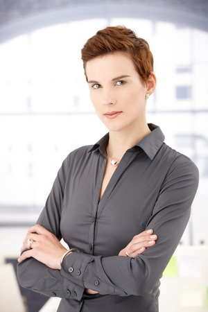 Portrait of smart woman with trendy hair style standing with arms folded, looking at camera. photo