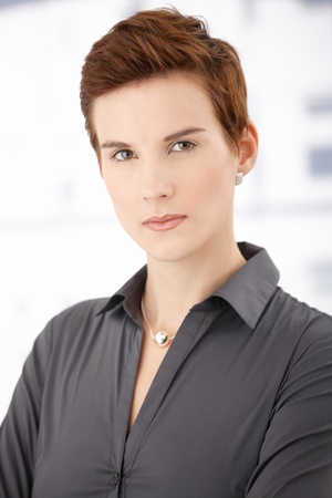 offish: Portrait of trendy ginger woman with short hair style, looking at camera.