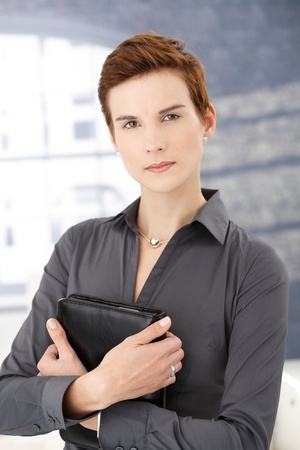 Determined businesswoman standing in office holding organizer, looking at camera. photo