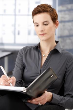 taking note: Businesswoman prendere appunti a personal organizer in ufficio. Archivio Fotografico